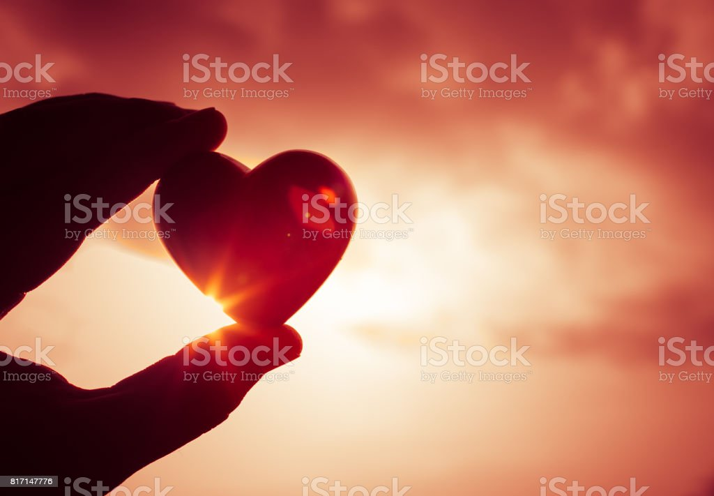 Hand holding beautiful heart up to the sky. stock photo
