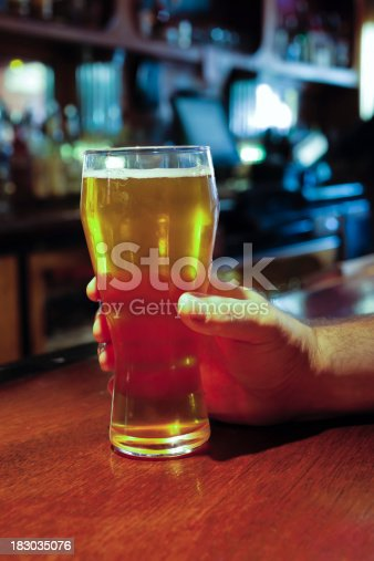 istock Hand Holding Beer Glass on a Pub Bar 183035076