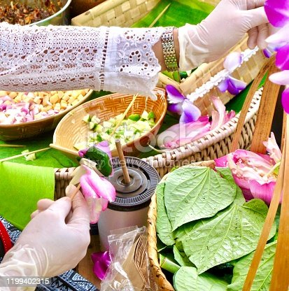 Thai Traditional Snack and Dessert, Hand Holding Miang Kum or Sweet and Spicy Betel Leaf and Lotus Petal Wrap Filled with Coconut, Peanuts, Dried Shrimp, Chiles and Lime.