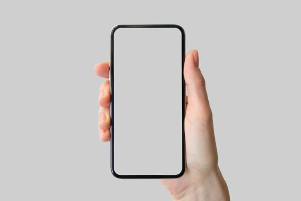 Hand holding bezel-free / frameless modern smartphone in front of neutral background stock photo