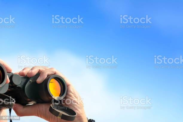 Hand holding binoculars on blue sky background picture id928181566?b=1&k=6&m=928181566&s=612x612&h=a5xzwgha27 hvbiazgvrksy707pfhfod vad46q6yza=