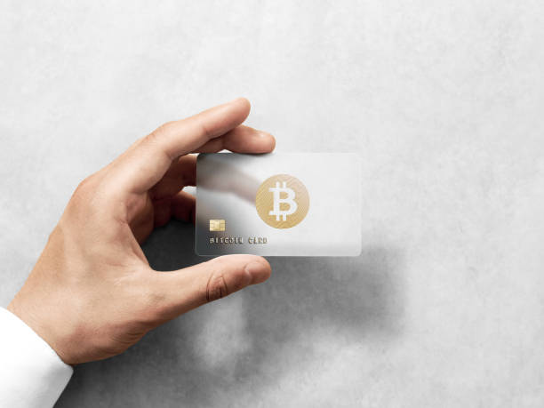 Hand holding bitcoin card template with embossed gold logo stock photo