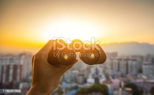 Hand holding black binoculars at city sunset