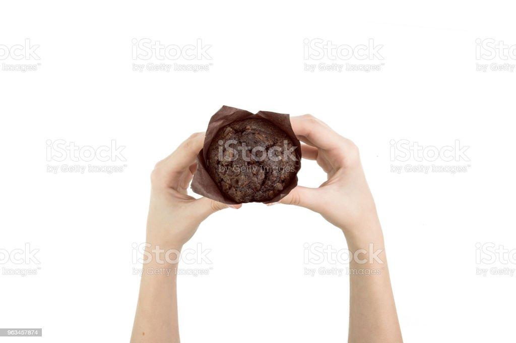Siyah kakao Muffin çikolata parçaları ile izole kağıt üstten görünüm pişirme üzerinde tutan el - Royalty-free Atıştırmalıklar Stok görsel