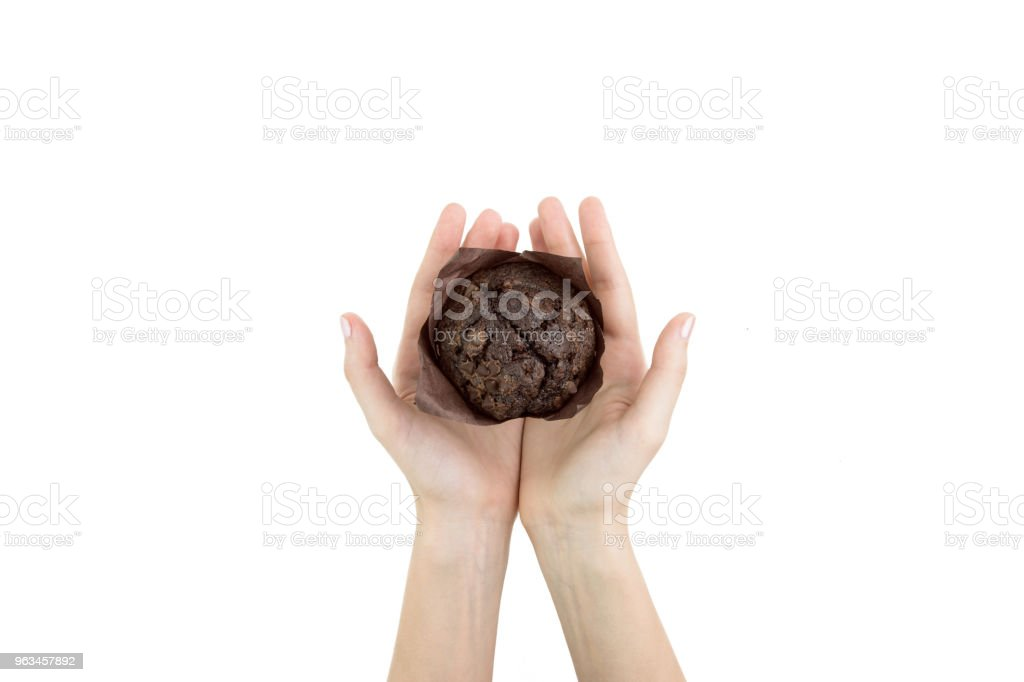 Hand Holding Black Cocoa Muffin With Chocolate Chips On It In Baking Paper Isolated Top View - Zbiór zdjęć royalty-free (Białe tło)