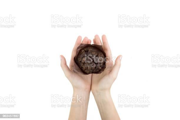 Hand Holding Black Cocoa Muffin Z Czekoladowymi Chipsami Na Nim W Papierze Do Pieczenia Izolowane Top View - zdjęcia stockowe i więcej obrazów Białe tło