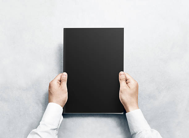 hand holding black magazine with blank cover mockup. - magazine cover stock photos and pictures