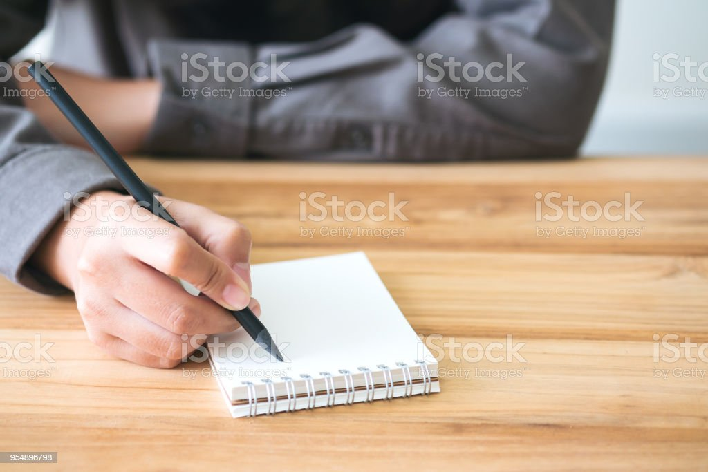A hand holding black pencil writing on notebook on vintage wooden...