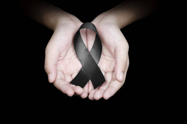Hand holding black ribbon on black background mourning awareness sign Hand holding black ribbon on black background mourning awareness sign mourning stock pictures, royalty-free photos & images