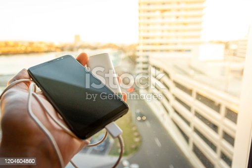 Hand holding black smartphone (mobile pohone) which is being charged with a battery power bank against the sunlight through the window, urbanized area in defocused background