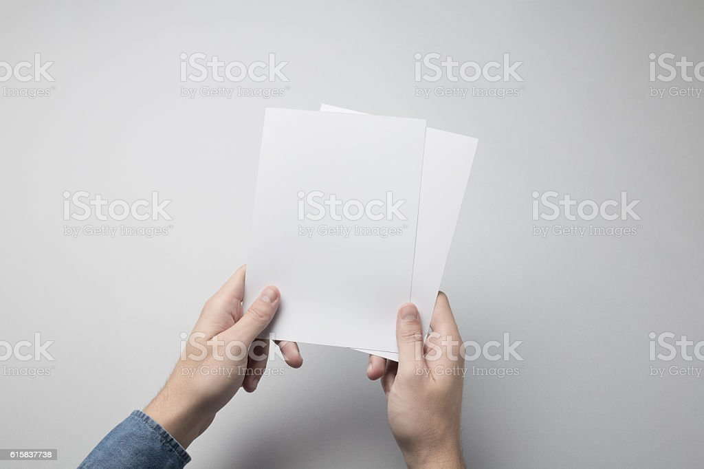 Hand holding Blank A5 Flyer / Invitation Mock-up. stock photo