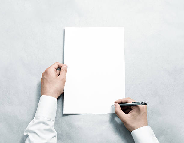 Hand holding blank agreement mockup and signing it. - foto de stock