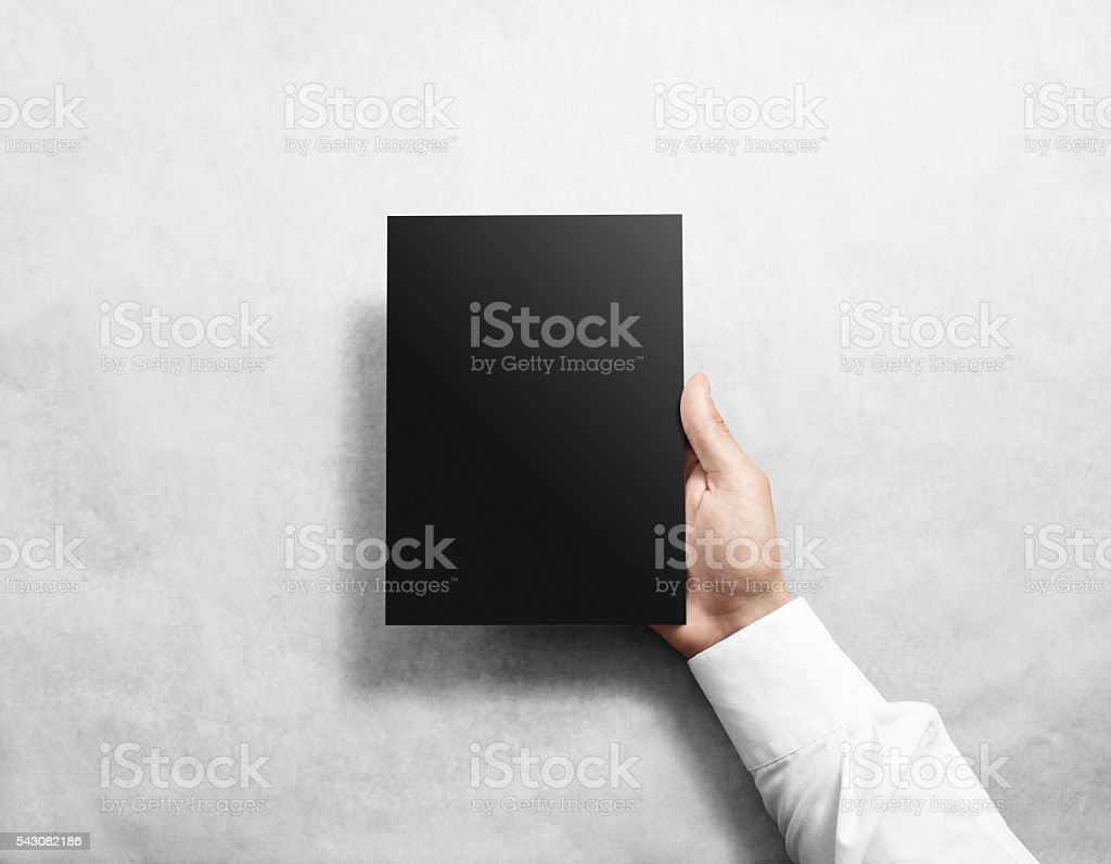 Hand holding blank black brochure booklet mockup. stock photo