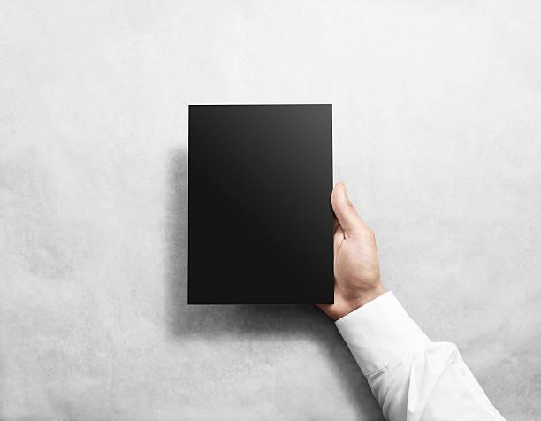 Hand holding blank black brochure booklet mockup. stock photo