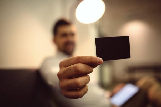 Mão segurando a vista de frente do cartão de crédito em branco preto maquete. Projeto de banco-cartão plástico simulado acima - foto de acervo