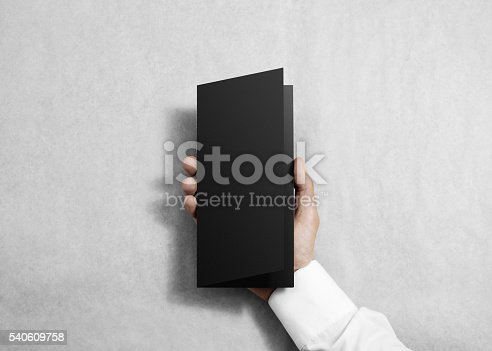 istock Hand holding blank black opened brochure booklet. 540609758