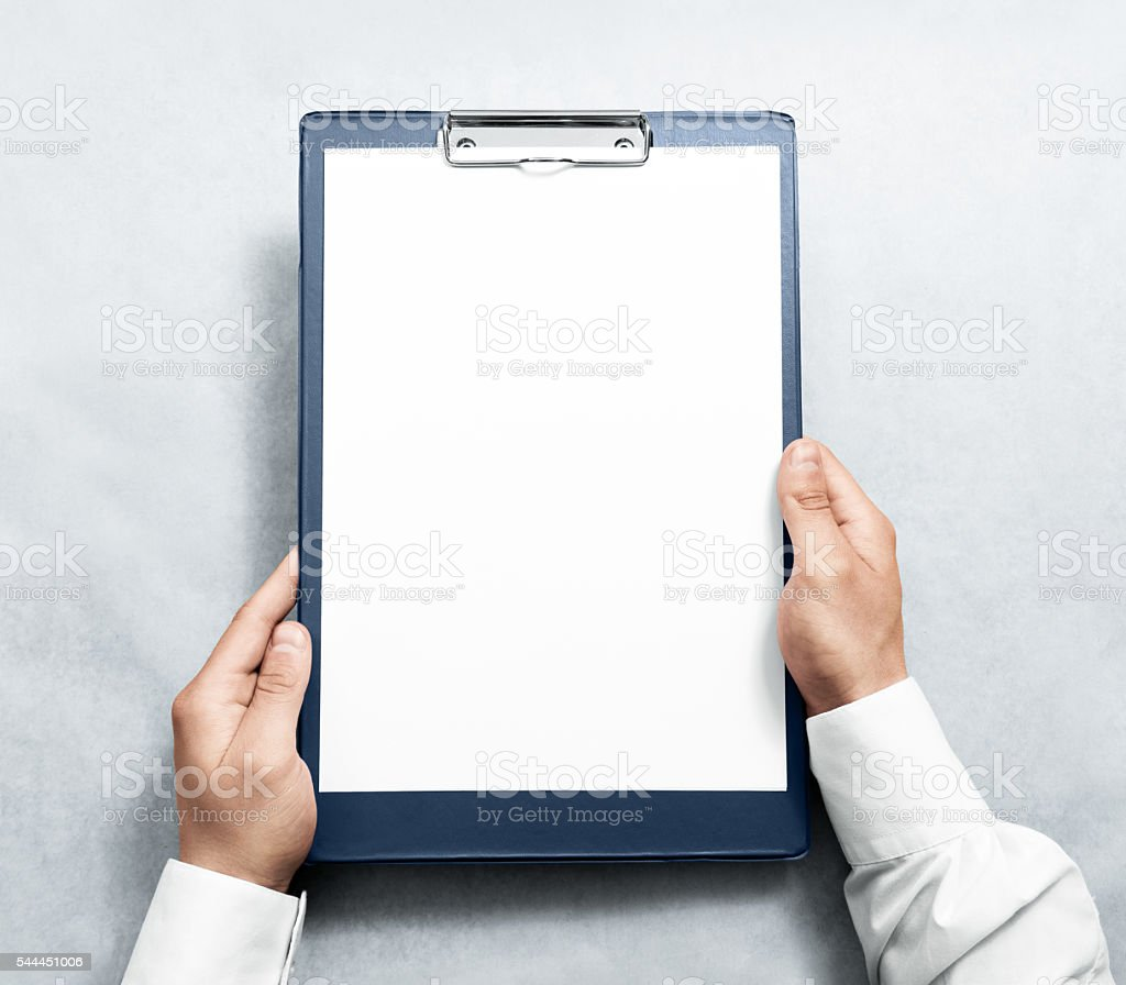Hand holding blank clipboard with white a4 paper design mockup. stock photo