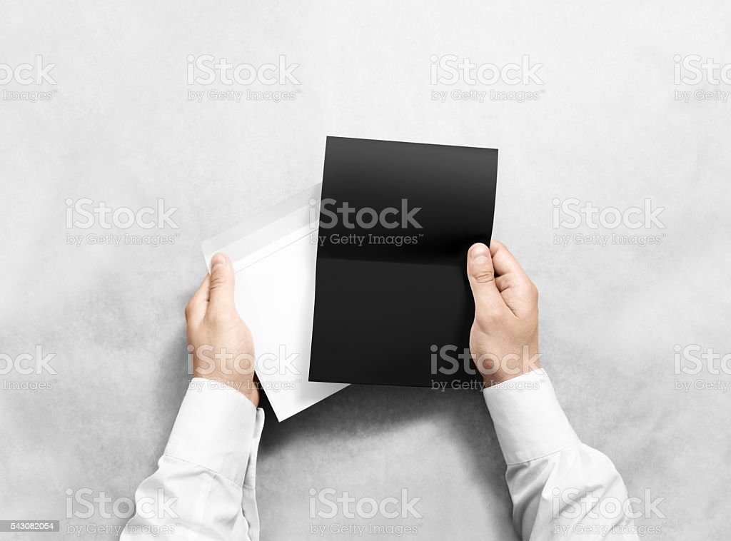 Hand holding blank envelope and black letter mockup, isolated. stock photo