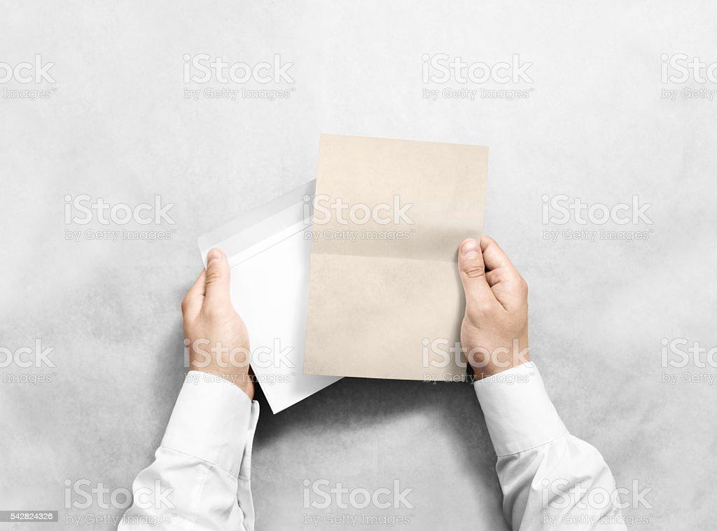 Hand holding blank envelope and kraft letter mockup, isolated. stock photo