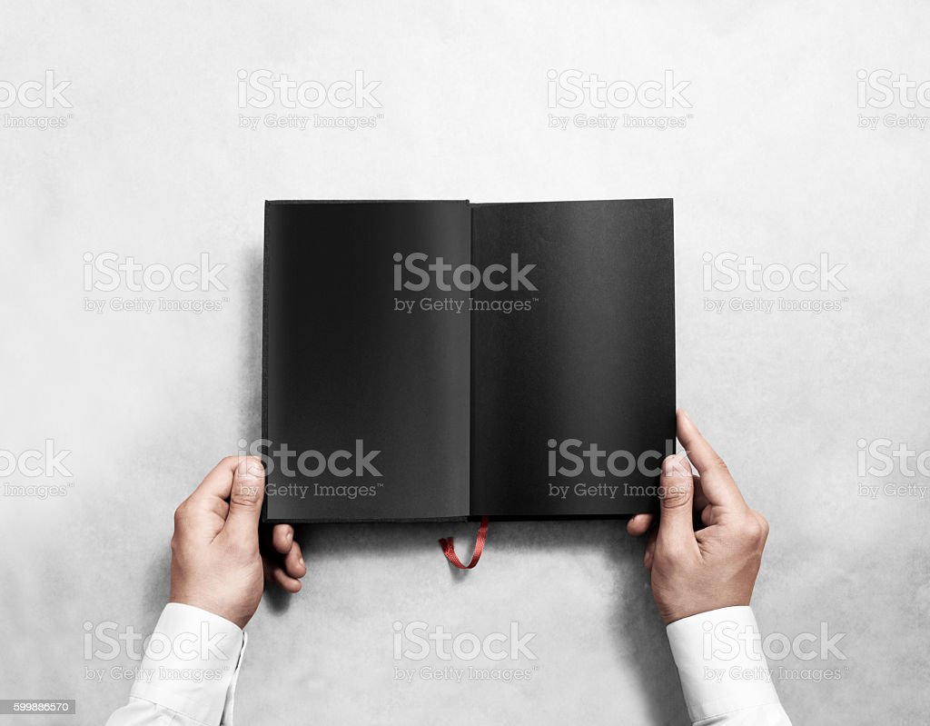 Hand holding blank opened book mock up with black pages. stock photo