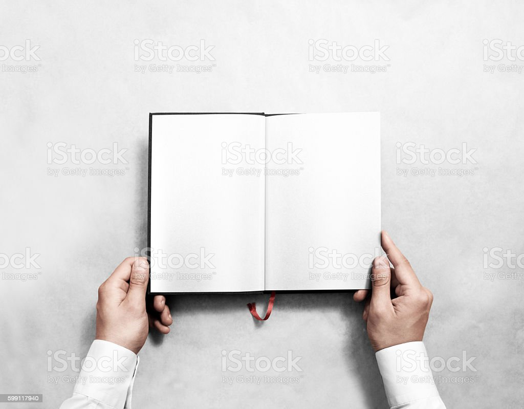 Hand holding blank opened book mock up with white pages. stock photo
