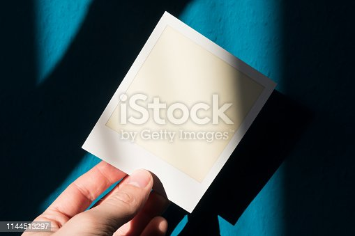 1183352589 istock photo hand holding blank or empty instant film frame 1144513297