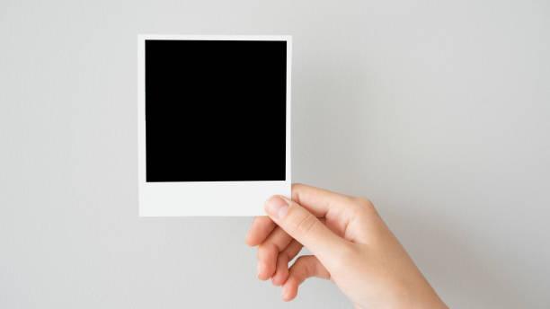 hand holding blank photo frame - polaroid foto e immagini stock