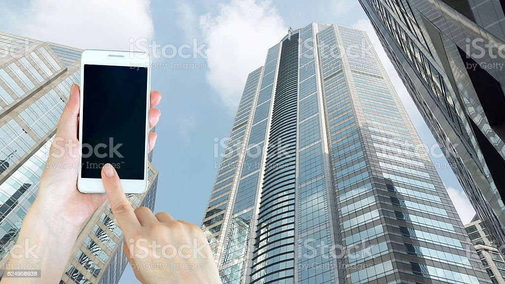 Hand holding blank screen smart phone with buiding background stock photo