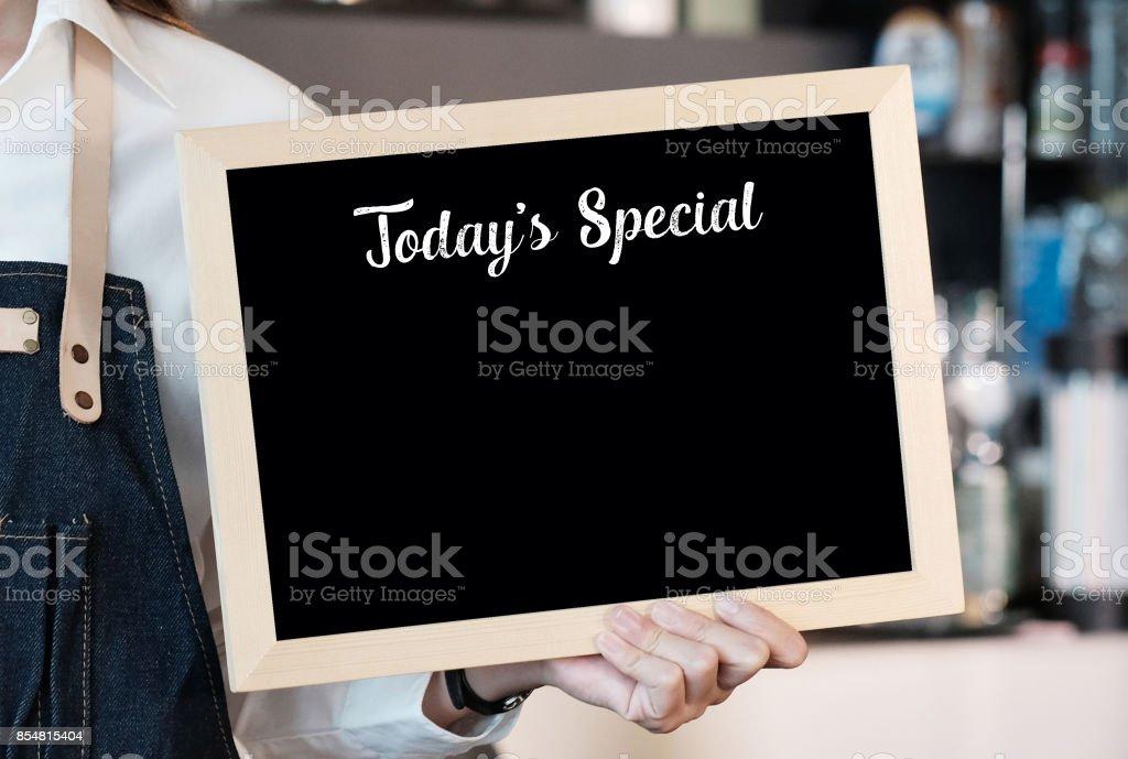 Hand halten heutigen Spezialplatte über Unschärfe Café Hintergrund leer ist, Raum für Text, Essen und trinken Hintergrund kopieren – Foto