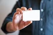 istock Hand holding blank white credit card mockup front side view. Plastic bank-card design mock up 844190384
