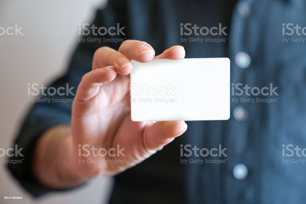Hand holding blank white credit card mockup front side view. Plastic bank-card design mock up stock photo