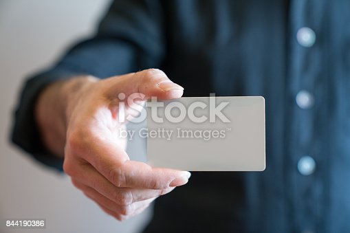 844190384 istock photo Hand holding blank white credit card mockup front side view. Plastic bank-card design mock up 844190386
