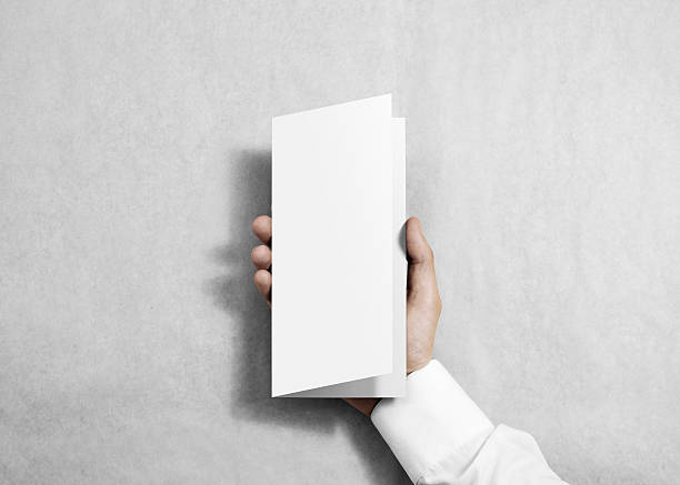 Hand holding blank white flyer brochure booklet in the hand. stock photo
