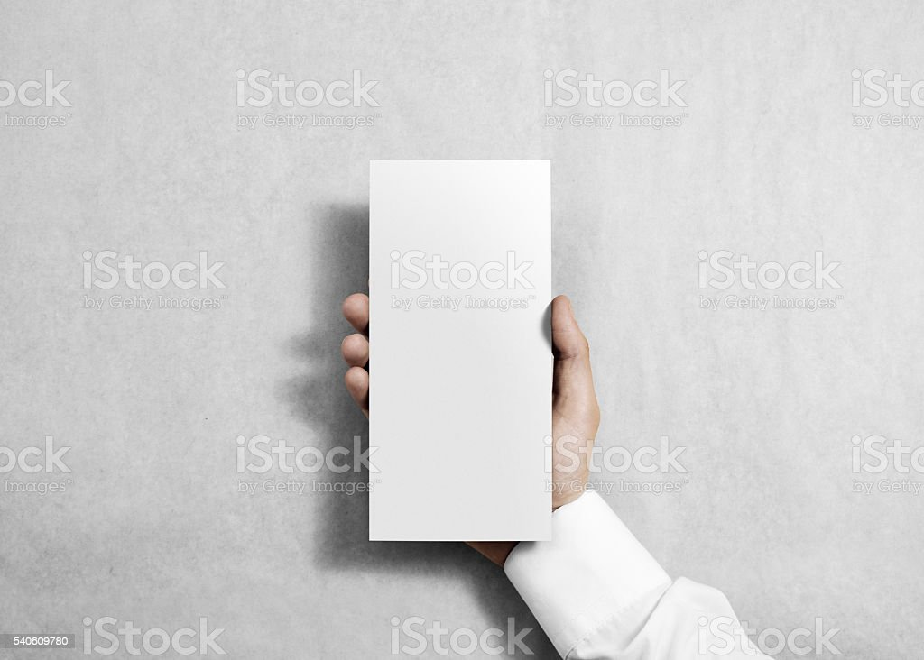 Hand holding blank white flyer brochure booklet. stock photo