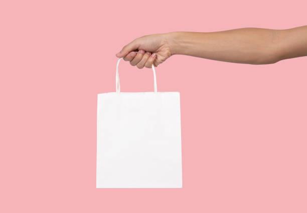 Hand, die leere weiße Papiertüte für Mockup Vorlage Werbung und branding isoliert auf rosa Hintergrund. – Foto