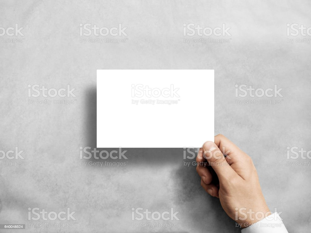 Hand holding blank white postcard flyer in the . stock photo