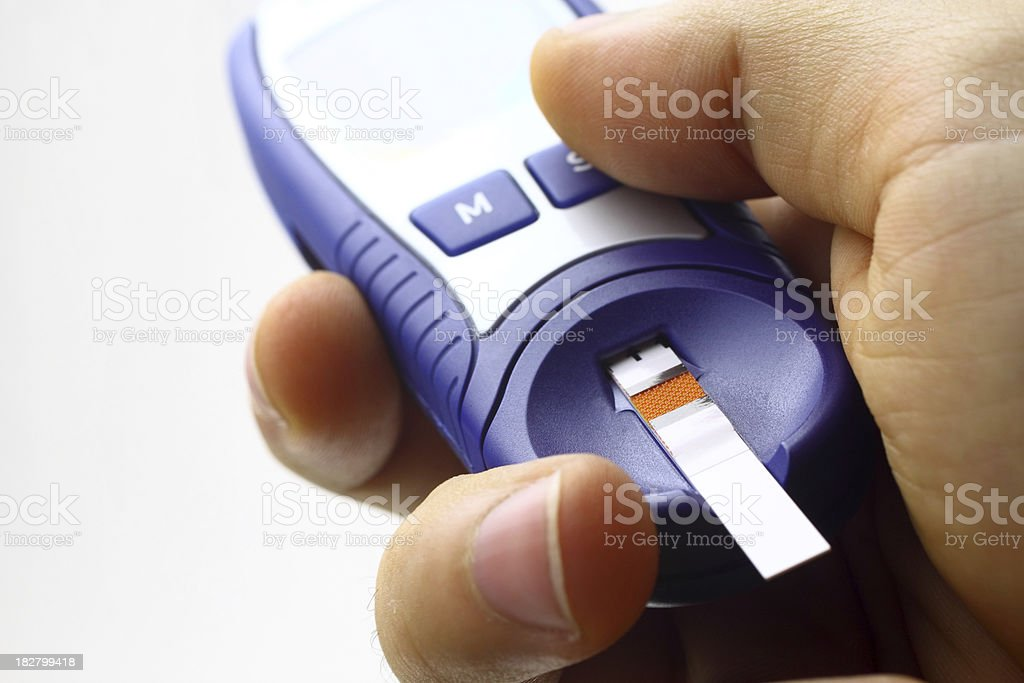 Hand holding blood sugar test device stock photo