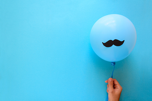 Hand holding blue balloon with a paper mustache on blue paper background. Cut out style. Movember  or man health concept. Top view. Flat lay. Copy space