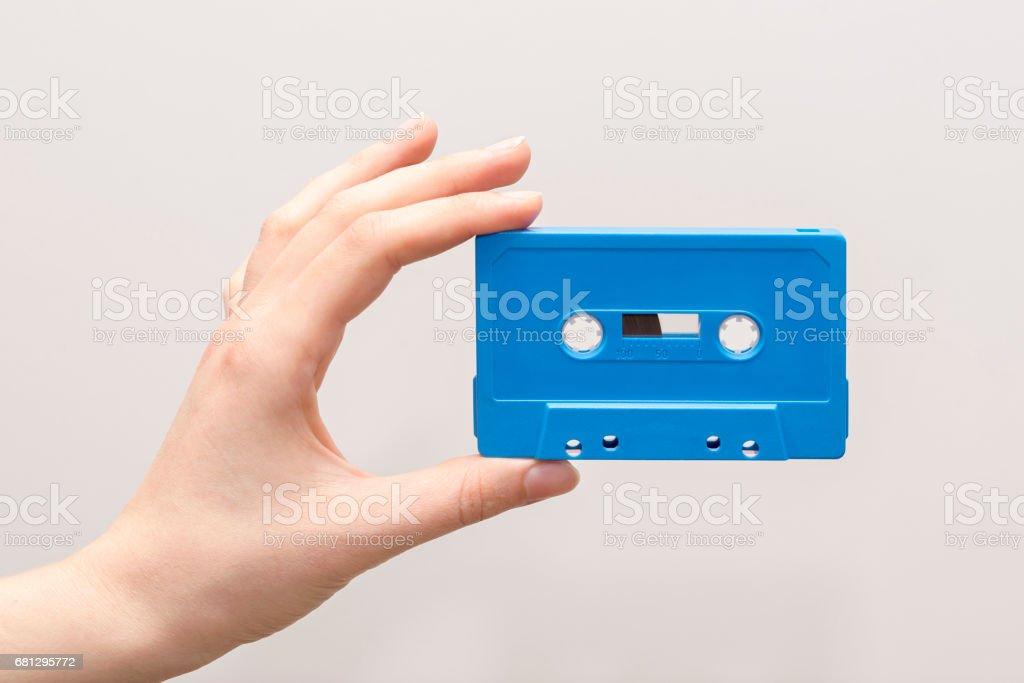 hand holding blue cassette tape stock photo