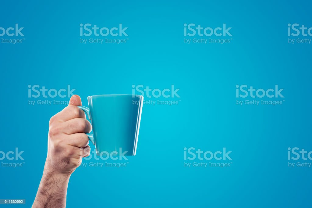 Hand holding blue cup on blue background stock photo