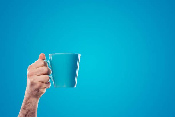 mano que sujeta la taza azul sobre fondo azul - taza fotografías e imágenes de stock