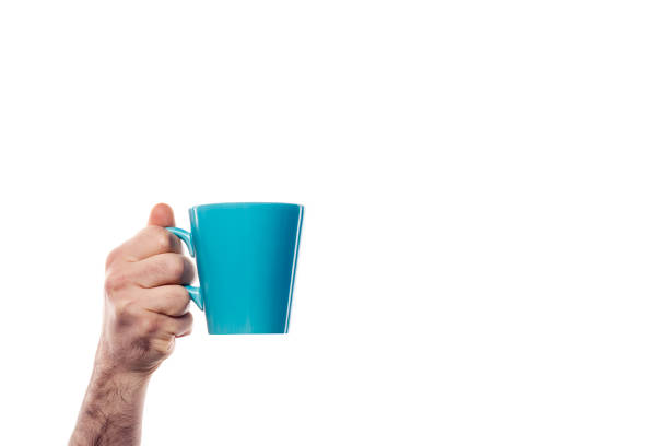 Hand holding blue cup on white background stock photo