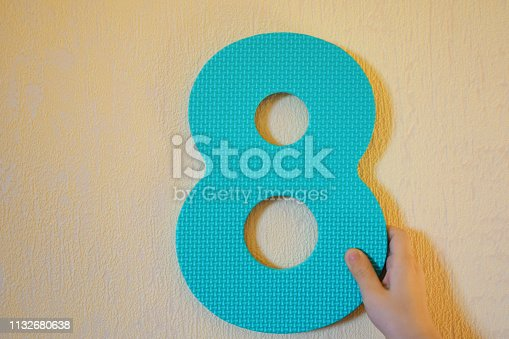 Hand holding blue number eight on yellow wall background with copy space for text. 8 anniversary birthday design or educational children toys for learning colors and numbers concept.