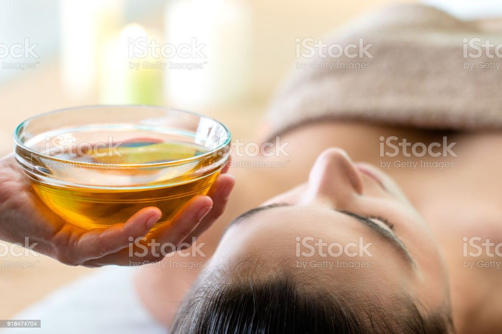 Hand holding bowl with aromatic oil in spa. stock photo
