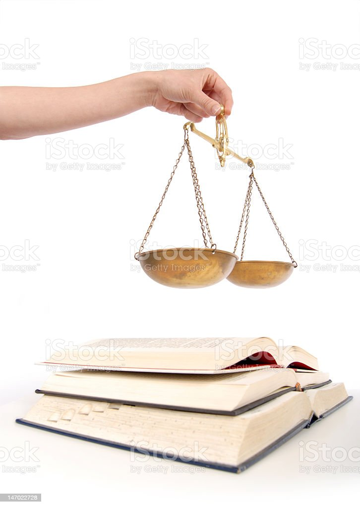 Hand holding brass scales over legal books royalty-free stock photo