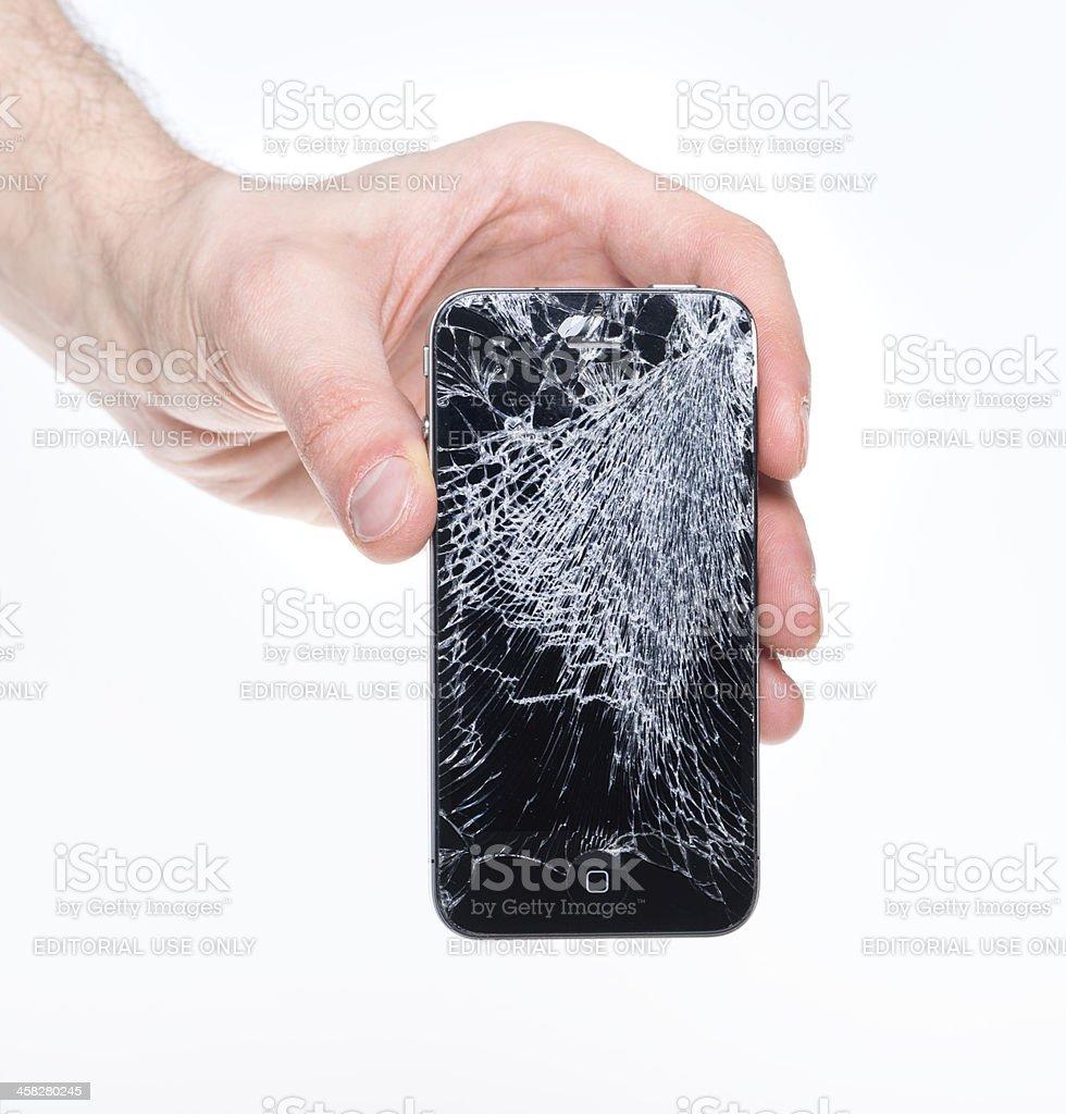 Hand holding broken Apple iPhone 4 royalty-free stock photo