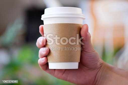 Man hand holding brown paper cup of hot coffee in cafe.