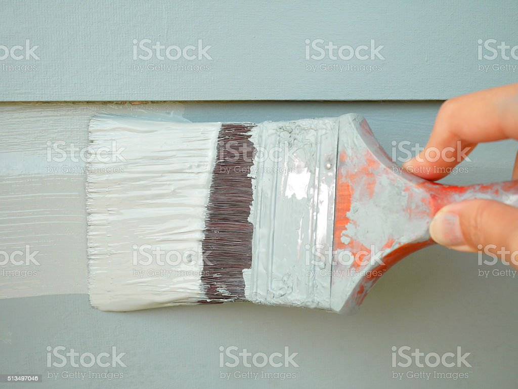 Hand holding brush painting wall stock photo