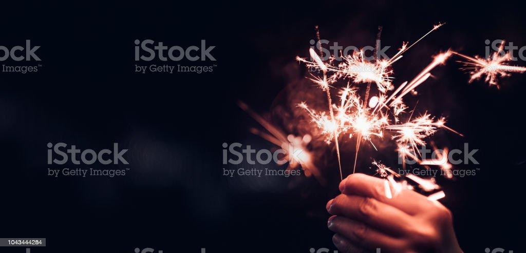 Hand holding burning Sparkler blast on a black bokeh background at night,holiday celebration event party,dark vintage tone Hand holding burning Sparkler blast on a black bokeh background at night,holiday celebration event party,dark vintage tone Backgrounds Stock Photo