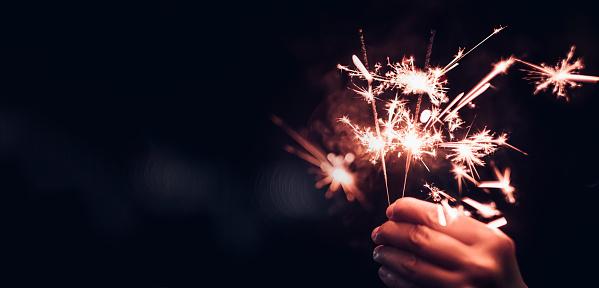 Hand Holding Burning Sparkler Blast On A Black Bokeh Background At Nightholiday Celebration Event Partydark Vintage Tone Stock Photo - Download Image Now